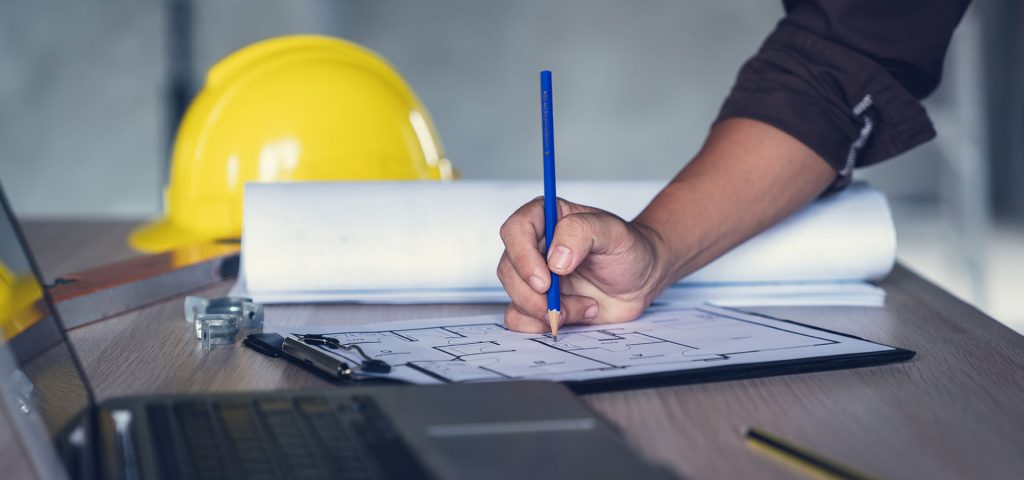man drawing on a commercial blueprint